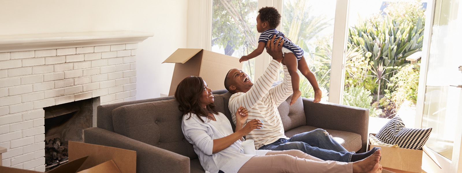 family in living room playing with and holding child above their heads