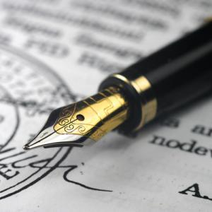 A fountain pen rests on a legal document